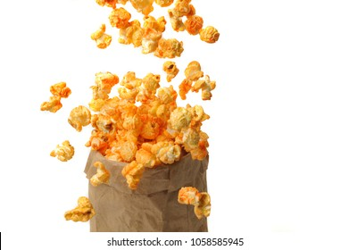 large air grains of yellow delicious roasted popcorn in a craft pack fly up against a white background