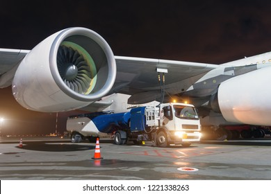 Large aircraft jet engines, Fueling a huge airplane, a truck with fuel with hoses connected to a fuel tank