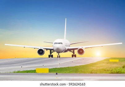 Large aircraft on taxiing sunset at the airport, the sky is the sun and the steering track