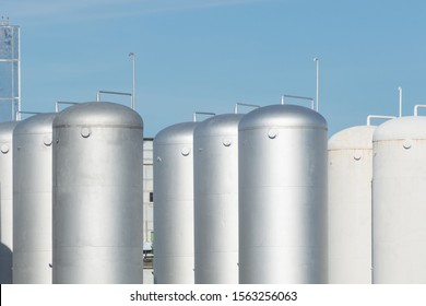 Large aluminum containers for storing near nuclear power plant. Metal elevator. Modern aluminum or steel storage tanks or barrels against the blue sky