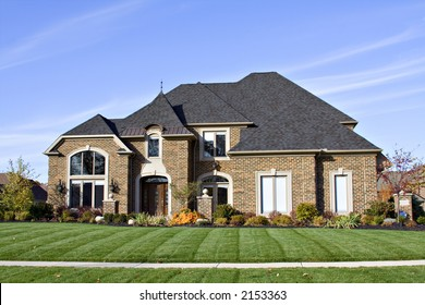 A large American brick home with many roof angles and windows.