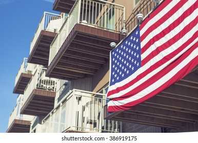 large american flag draped over balcony looking up at apartment complex.