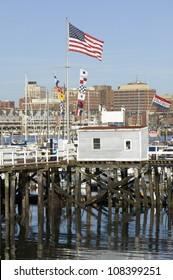 Large American flag flies in Portland Harbor with south Portland skyline, Portland, Maine