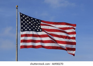A large American flag flying against blue sky.