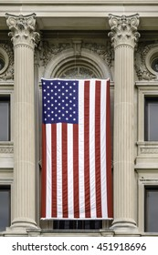 Large American flag hanging in front of DeKalb County Courthouse, built in Classical Revival style, in Sycamore, Illinois, USA, for themes of national holidays, service, and ideals