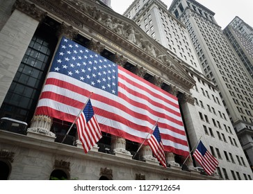 Large American flag on the exterior of the New York Stock Exchange on the 4th of July. July 4, 2018 - New York City, New York, USA.