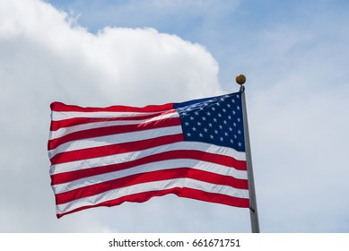 Large American flag waving on flag pole with cloud blue sky. Windy and sunny day with waving star and striped flag blowing/flowing. Ruffled USA flag. Room for text.