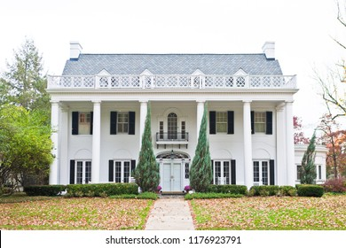 Large American white style neoclassical mansion with white columns and black shutters.