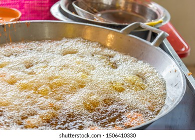 Large amount of boiling oil in a big pan for frying.