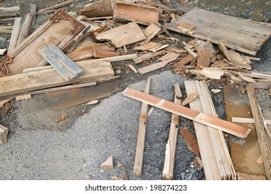 A large amount of discarded home repair lumber and cabinet doors on top of old asphalt.