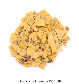 A large amount of peanut brittle candy on a white background.