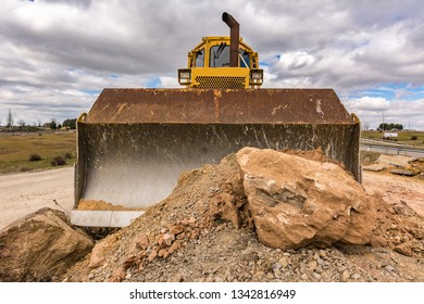 Large amount of stone and earth moved by a yellow excavator