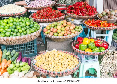 Large amounts of vegetables on display at a market in Hanoi, Vietnam, including peppers, limes, chilli, carrots and cucumbers