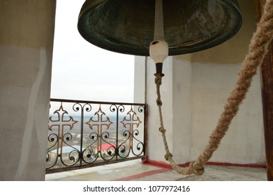 A large ancient bell on the bell tower. View of the city through the lattice