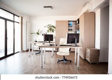 Large angle view. Interior of an empty modern office with an empty desk. Business and workplace. Clean interior of a corporate company