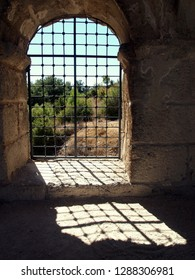 Large arched stone window with a square decorative grid. Plus game of light and shade. Taken at the upper rows of the Aspendos Theater in Turkey.
