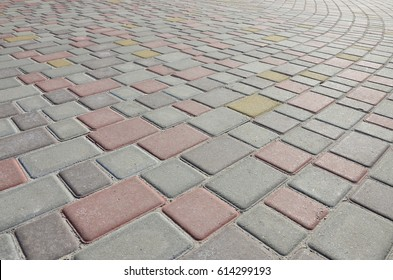 A large area, laid out of paving stone in perspective. Detailed photo of paving stones in the sidewalk avenue close-up