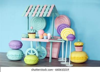 Large artificial sweets in the interior, different pastel colors. Photozone. Candy shop, huge colorful props, colorful fake lollipop sweets in pastel blue stylish summer outfit.