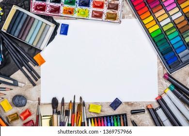 Large artist accessories set. Collections of paint brushes, tube paint, watercolor paints, pastel. Artist workshop background