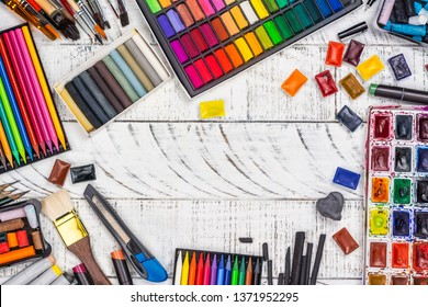 Large artist accessories set. Collections of paint brushes, tube paint, watercolor paints, pastel. Artist workshop background