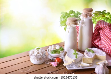 Large assortment of artisanal dairy products on a wooden table with green background. Elevated view. Horizontal composition