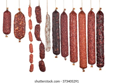 a large assortment of vertically arranged salami sausages isolated on white background