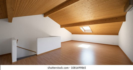Large attic with wooden floors and exposed beams. White walls, perfect for copy-sace
