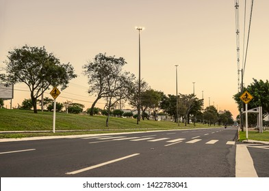 Large avenue with crosswalk. Pedestrians sign.  Avenue with trees around, tall light poles and few traffic at a sunset. Photo at the Afonso Pena avenue, Campo Grande - MS, Brazil.