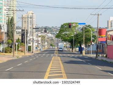 Large avenue with four lanes, few cars on the street, local commerce and buildings around. Photo on the middle of the avenue. Ceara avenue at Campo Grande MS, Brazil.