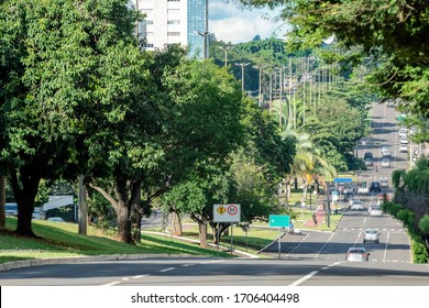 Large avenue surrounded by big green trees of a wooded city. Photo taken at Afonso Pena avenue, Campo Grande - MS, Brazil.
