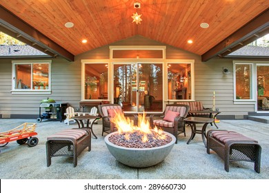 Large back yard with grass and covered patio with fire pit.