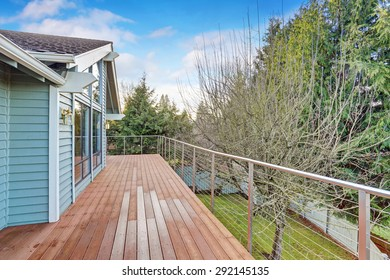 large backyard with grass and back deck.