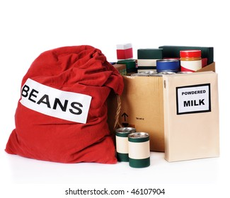 A large bag of beans, a box of powdered milk and multiple containers of nonperishable food to be given to the needy.  Isolated on white.