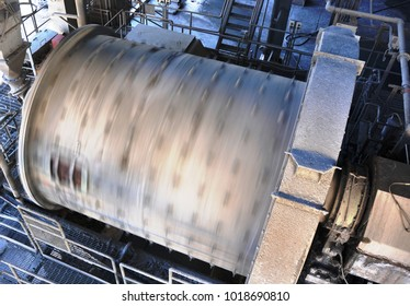 A large ball mill, visably spinning, to grind the gold ore it is fed.