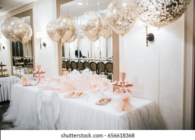 Large balloons hang over white dinner table with sweets