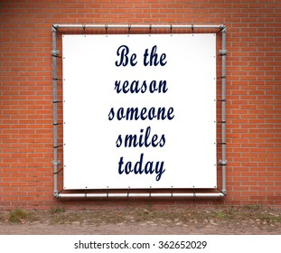 Large banner with inspirational quote on a brick wall - Be the reason someone smiles today