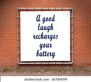 Large banner with inspirational quote on a brick wall - A good laugh recharges your battery