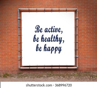 Large banner with inspirational quote on a brick wall - Be active, be healthy, be happy