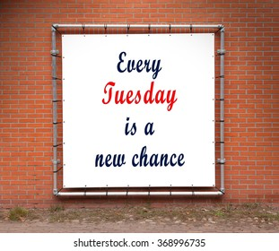 Large banner with inspirational quote on a brick wall - Every tuesday is a new chance