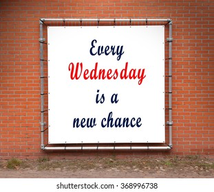 Large banner with inspirational quote on a brick wall - Every wednesday is a new chance