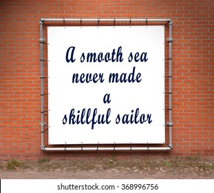 Large banner with inspirational quote on a brick wall - A smooth sea never made a skillful sailor