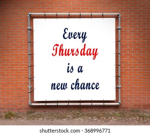 Large banner with inspirational quote on a brick wall - Every thursday is a new chance