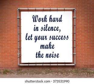 Large banner with inspirational quote on a brick wall - Work hard in silence...