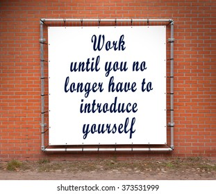 Large banner with inspirational quote on a brick wall - Work until you no longer...