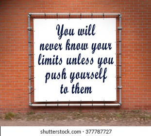 Large banner with inspirational quote on a brick wall - You will never know your limits...