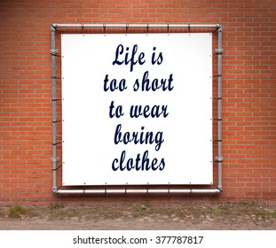 Large banner with inspirational quote on a brick wall - Life is to short to wear boring clothes