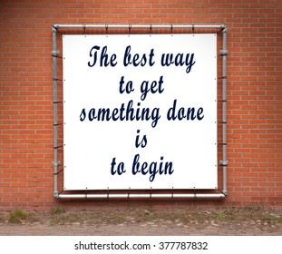 Large banner with inspirational quote on a brick wall - The best way to get something done is to begin