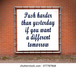 Large banner with inspirational quote on a brick wall - Push harder than yesterday...