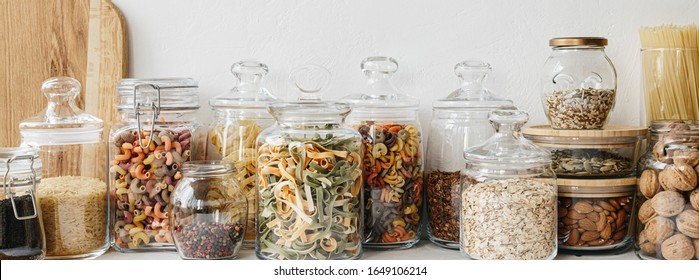 Large banner Various cereals and seeds in glass jars on the white textured background. Kitchen interior ideas. Eco friendly kitchen, zero waste home concept