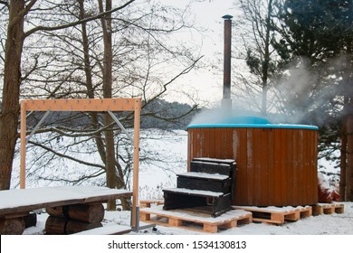 A large barrel of clean, hot water outdoors in a snow-covered forest. Winter swimming concept